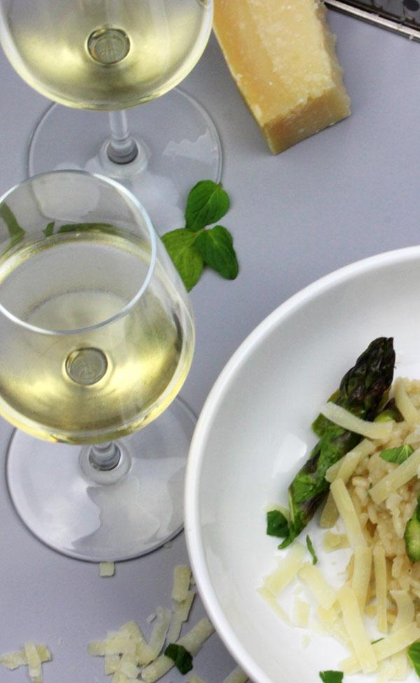 Angerichtetes Spargelrisotto mit Wein auf dem Tisch